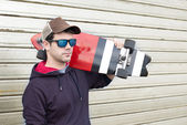 Portrait of man with skateboard and sunglasses on metalic backgr — Stok fotoğraf