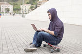 Man sitting on skateboard and laptop computer in the street. — Stock Photo