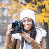 Portrait of smiling girl with bonnet and camera, autumn. — Stock Photo