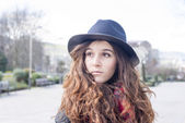 Portrait of casual attractive girl with hat in the street. — Photo