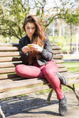 Girl using smart phone and sitting on wood bench, outdoor. — Стоковое фото