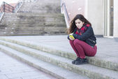 Serious and pensive young girl using mobile phone and sitting in the street. — Stock Photo