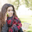 Attractive girl with scarf talking on mobile, outdoor. — Stock Photo