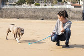 Woman with dog playing with ball in the beach. — Stock Photo