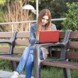Student laptop computer and sitting on bench in the park. — Stock Photo