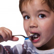 Little boy eats porridge — Stock Photo