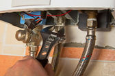 Repair of the gas water heater with adjustable wrench — Stockfoto