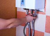 Hombre pone a prueba la fiabilidad de la fijación de las tuberías en el calentador de agua — Foto de Stock