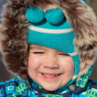 Stock Photo: Smiling little boy in a fur hood