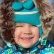 Smiling little boy in a fur hood — Stock Photo