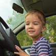Child playing behind the wheel of a car — Stockfoto
