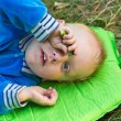 Little boy lying on green grass — Foto Stock