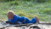 Little boy lying on green grass — Stockfoto