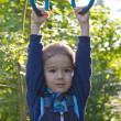 Stock Photo: Boy hanging on the rings