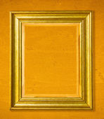 Wooden golden picture frame on cement — Stock Photo