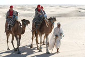 Beduin leading tourists on camels — Stok fotoğraf