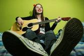 年轻的黑发女人床上弹吉他 — 图库照片