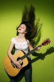 Young brunette playing guitar — Stock Photo