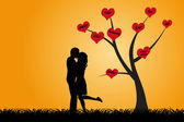 Kissing couple under the tree — Stock Photo