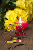 Yellow roses and candle — Stock fotografie