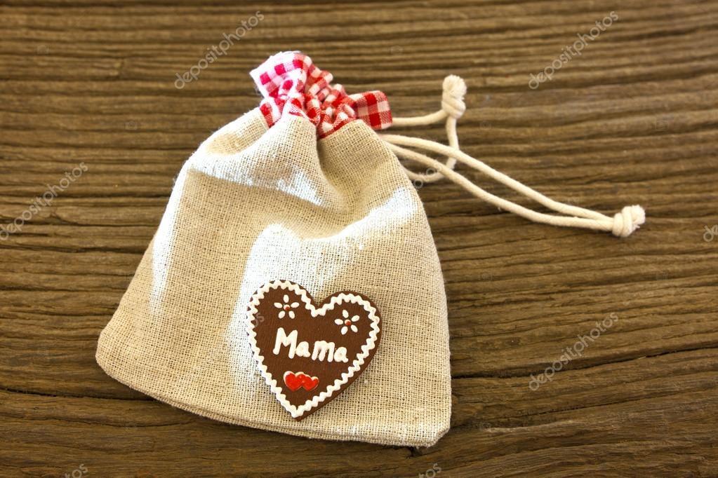 A small jute gift bag with label hearts on old wood plank — Stock Photo #18732575