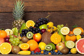 Fresh fruit in front of wooden wall — Stock Photo