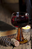 Glass of red wine with candle — Stock Photo