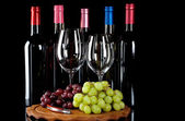 Wine bottles, wine glasses and grapes — Stock Photo