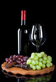 Red wine bottle with glass and grapes — Stock Photo