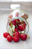 Fresh cherries in front of a preserving jar — Stock Photo