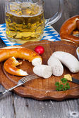 Veal sausage, pretzels and a glass of beer — Stock Photo