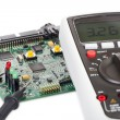 Digital multimeter and a circuit board — Stock Photo