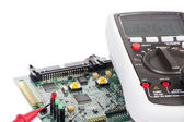 Digital multimeter and a circuit board — Stockfoto