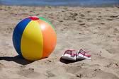 Beach Ball and Flip-Flops in the Sand — Stock Photo