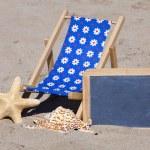 Beach scene with Sun Chair, Sunglasses and Blackboard — Stock Photo #33720891