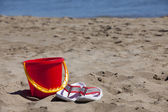 Flip-Flops and Bucket in the Sand — Stock Photo