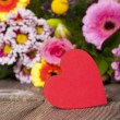 Stock Photo: Red heart in front of bouquet of flowers