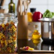 Stock Photo: Storage Jar with Colorful Pastand Cooking Spoon on Worktop