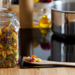 Stock Photo: Storage Jar with Pastand Cooking Spoon on Worktop