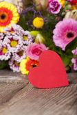 Red heart in front of a bouquet of flowers — Stock Photo