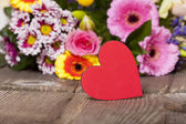 Red heart in front of a Bouquet — Stock Photo