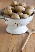 White Enamel Colander with raw potatoes — 图库照片