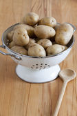 White Enamel Colander with raw potatoes and a cooking spoon — Stock Photo