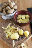 Raw potatoes and kitchen utensils on the worktop — Stock Photo
