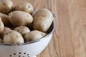 Close up of raw potatoes in a colander — Stock Photo