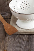 Enamel colander and a Cooking spoon stands on the kitchen table — Stock Photo