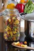 Large Storage Jar with Colorful Pasta and Cooking Spoon — Stock Photo