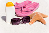 Sunscreen and flip-flops on the beach — Stock Photo