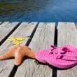 Flip flops and starfishes on a wooden pier — Stock Photo #50202411