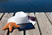 Tablet PC and straw hat at the swimming lake — Stock Photo